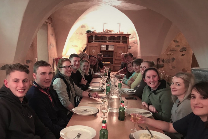 A group of guests eating dinner in a catered chalet