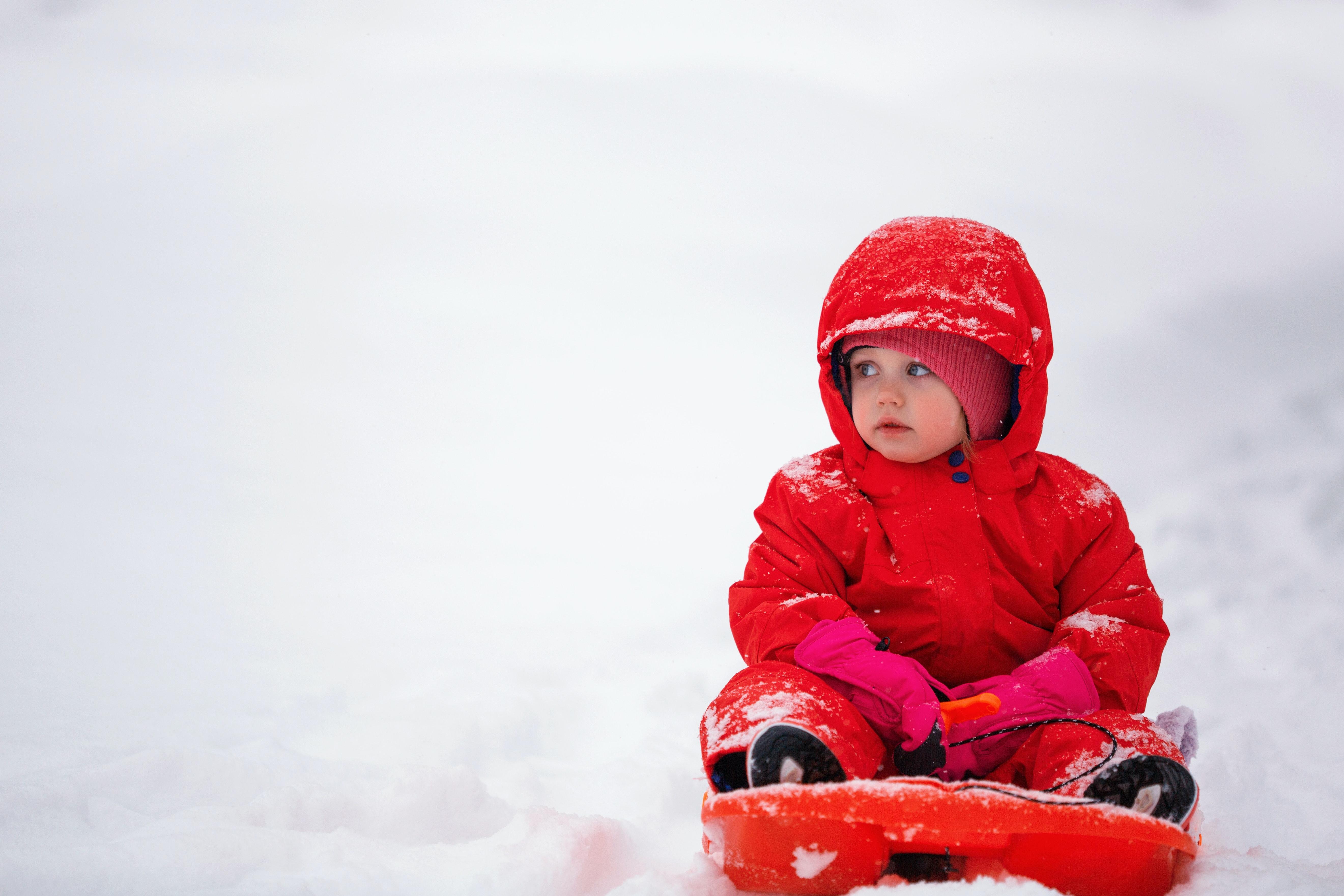 toddler dressed in red in a toboggan in a ski resort