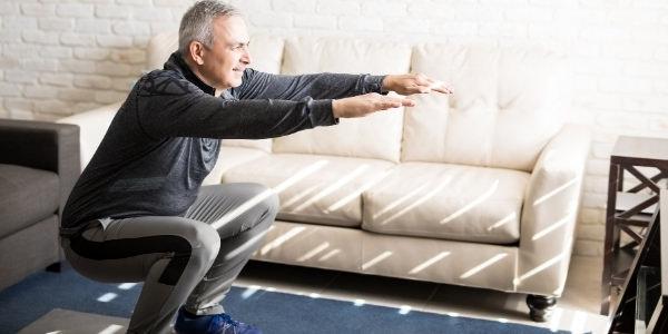 man doing a squat to improve ski fitness