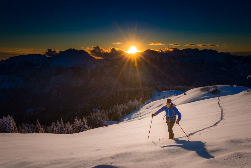 skier skinning up mountain at sunrise