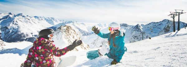 two snowboarders high fiving in meribel